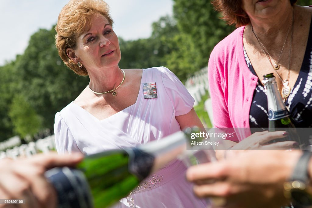Vickie Castro, left, of Corona, California, wearing a pin with a photo of her son Jonathan, and Karen Meredith of Mountain View, California, pour champagne as they gather with friends around the grave of Meredith's son Lt. Kenneth Ballard in Section 60, the burial ground for military personnel killed since 2001, at Arlington National Cemetery on May 30, 2016 in Arlington, Virginia. Both Ballard and Castro's son were killed in Iraq in 2004. The women have been gathering with others at the grave every year since to celebrate their sons' lives.