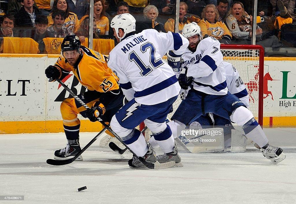Vicktor Stalberg of the Nashville Predators skates against Ryan Malone of the Tampa Bay Lightning at Bridgestone Arena on February 27 2014 in...