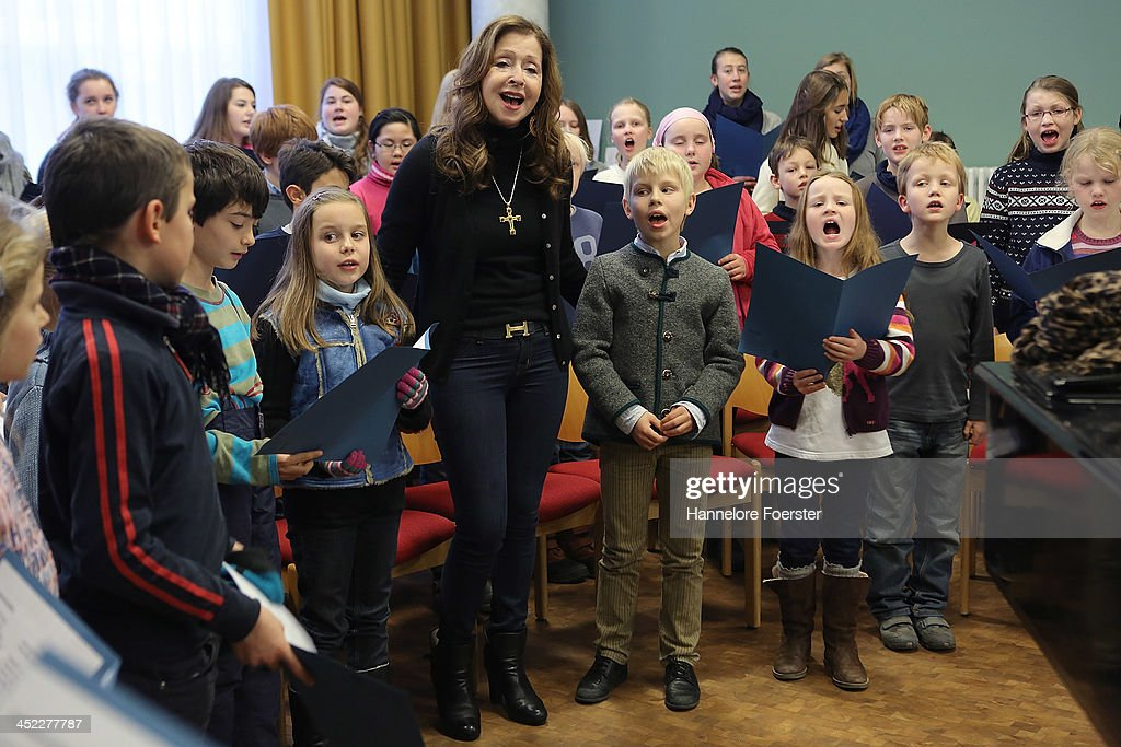 Vicky Leandros rehearses with the Kinderchor der Domsinschule at the Christmas market at Roemerberg square on its opening day on November 27 2013 in...