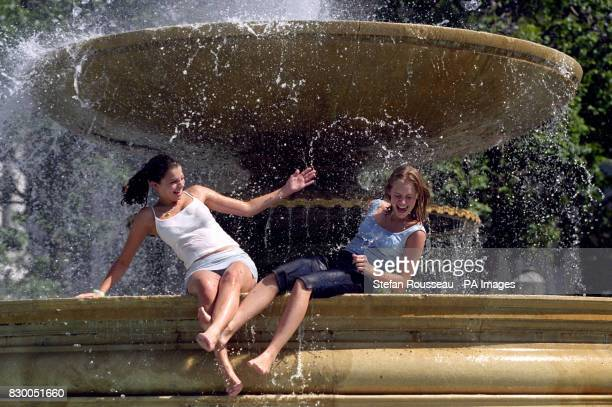 Vicky Woodcock and Nicola Wilden from Essex splash around in the fountains in Trafalgar Square in London on one of the hottest days of the year as...