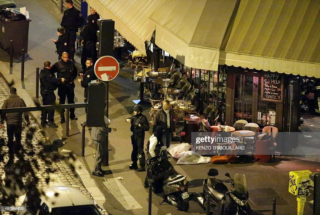 A victim lies on the ground covered by a white sheet outside of the cafe 'A la Bonne Biere' in Paris on November 13 2015 following an attack Over 100...