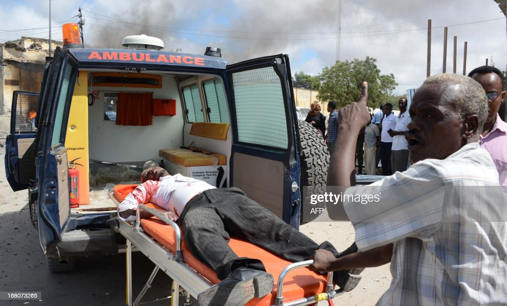 A victim of a suicide attack is carried on a stretcher on May 5, 2013 after a suicide attacker rammed a car laden with explosives into a government convoy at a busy junction in Mogadishu. Around 11 people were killed. The blast is the latest in a string of bloody attacks in the seaside capital, where Al-Qaeda linked Shebab insurgents have vowed to topple the government and have set off several bombs and launched guerrilla-style strikes. AFP PHOTO / Mohamed Abdiwahab