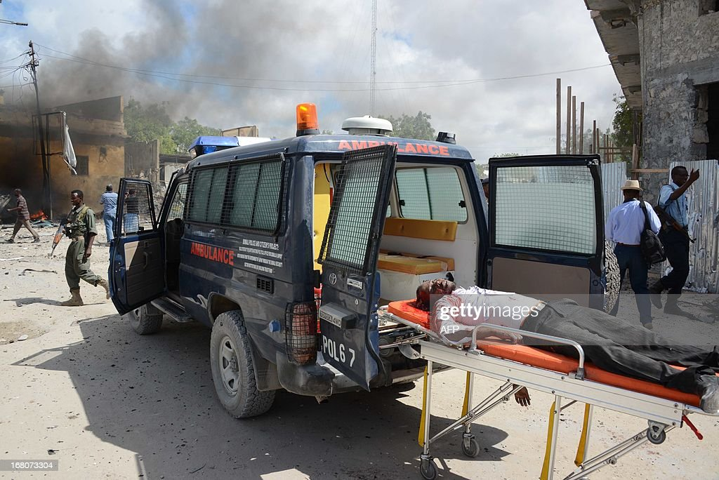 A victim of a suicide attack is on a stretcher on May 5, 2013 after a suicide attacker rammed a car laden with explosives into a government convoy at a busy junction in Mogadishu. Around 11 people were killed. The blast is the latest in a string of bloody attacks in the seaside capital, where Al-Qaeda linked Shebab insurgents have vowed to topple the government and have set off several bombs and launched guerrilla-style strikes. AFP PHOTO / Mohamed Abdiwahab