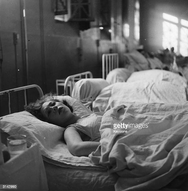 A victim of bombing raids on Paris lies in a hospital bed