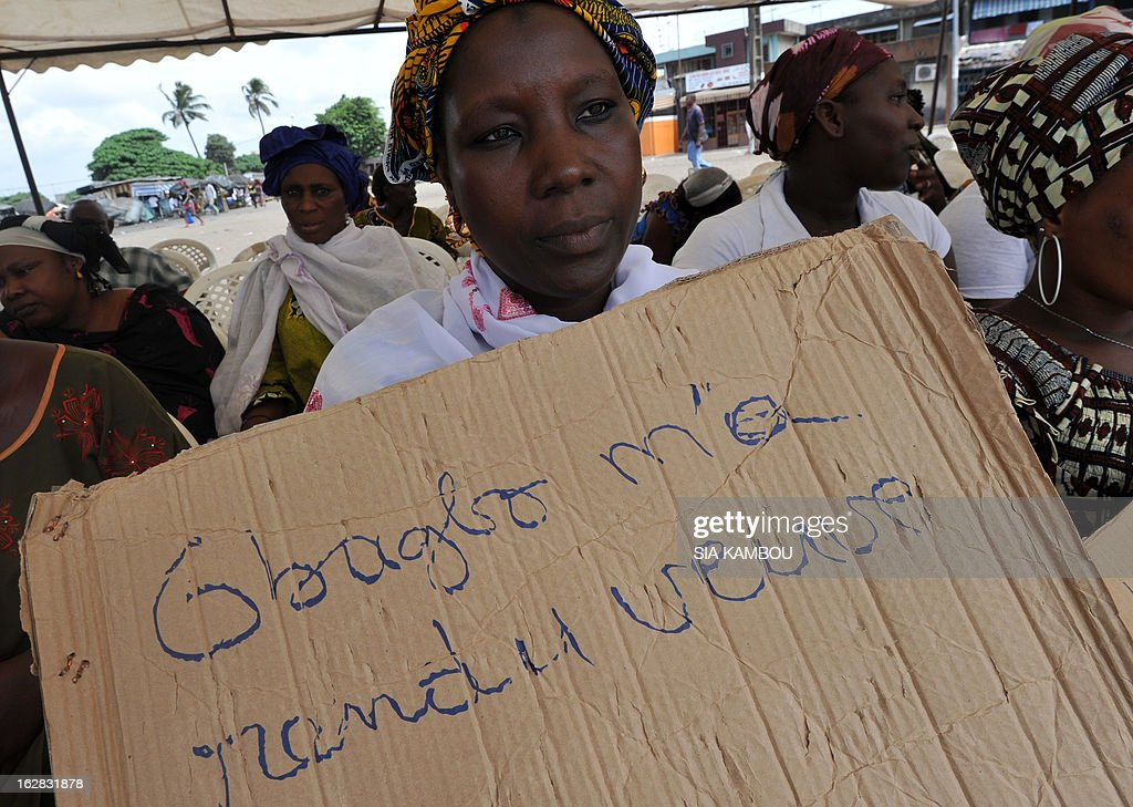 A victim of the 2010 post-election crisis hold a placard reading 'Gbagbo turned me into a widow' during a gathering in the Kouassai popular district of Abidjan on February 28, 2013. Former Ivory Coast president Laurent Gbagbo is expected to address the International Criminal Court on the final day of hearings today to decide whether he should face trial for crimes against humanity during the bloody 2010-2011 election standoff. AFP PHOTO/ SIA KAMBOU