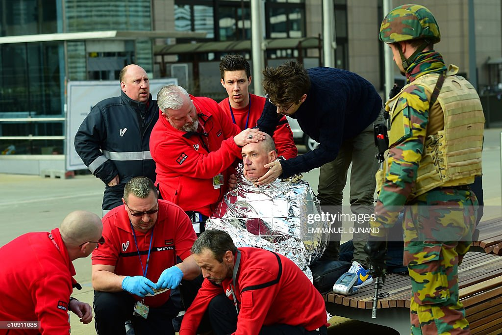 A victim receives first aid by rescuers, on March 22, 2016 near Maalbeek - Maelbeek metro station in Brussels, after a blast at this station near the EU institutions caused deaths and injuries.