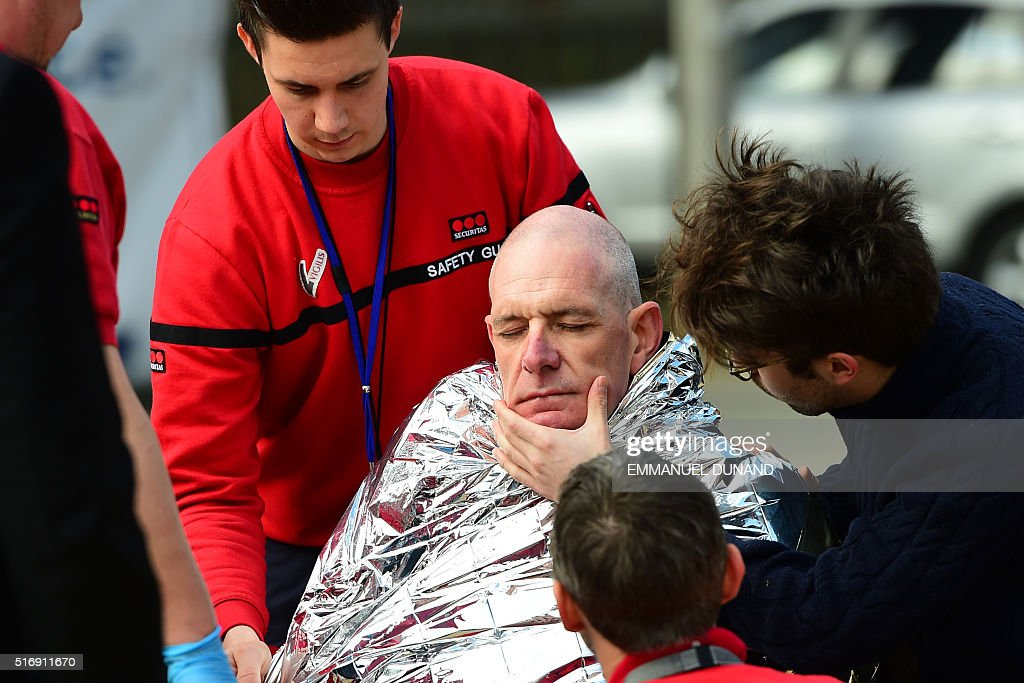 TOPSHOT A victim receives first aid by rescuers on March 22 2016 near Maalbeek Maelbeek metro station in Brussels after a blast at this station near...