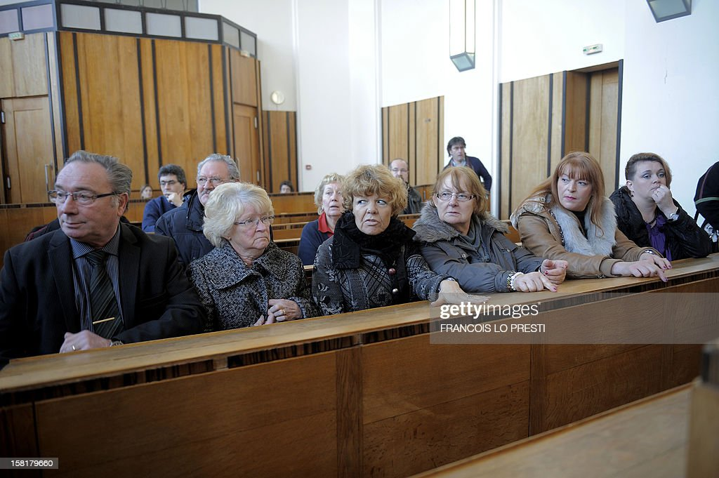 Victims and families of victims sit in the Bethune courthouse, northern France on December 10, 2012 during the opening day of the trial against petrochemical plant Noroxo for contanimination. Noroxo, part of the Exxon Mobile group, the world's biggest oil producer is tried in a case of an epidemic legionellosis , whose source of contamination was identified as the Noroxo factory in Harnes, and contracted over the 2003 and 2004 period making 83 victims, fourteen of which died. AFP PHOTO / Francois LO