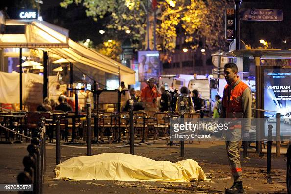 A victim's body lies covered on Boulevard des Filles du Calvaire close to the Bataclan theater early on November 14 2015 in Paris France According to...