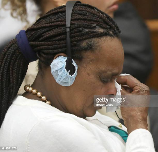 A victim's family member dabs tears during testimony of Sergeant Detective Daniel Duff while wearing earphones for translation The double murder...