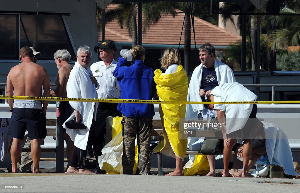 Victims from a dive boat that capsized off Hillsboro Inlet near Pompano Beach, Florida, wait wrapped in towels and yellow tarps at the Hillsboro Inlet Marina, as Florida Wildlife officers and Broward sheriff deputies investigate the incident, Thursday, November 22, 2012. Four people were transported to an area hospital, one in critical condition, after a commercial dive boat was hit by a massive wave and capsized just outside Hillsboro Inlet.