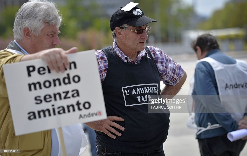 A victims of cancer-causing asbestos holds a placard reading in Italian 'For a World without asbestos' stands near a man wearing a pullover reading in French 'abestos kills'during a demonstration on May 7, 2013 at the place des Nations facing the United Nations office in Geneva. Several national associations for the defence of the asbestos victims staged a protest during the 6th metting of the Rotterdam conventions for the listing of chrysotile asbestos on the list of dangerous products.