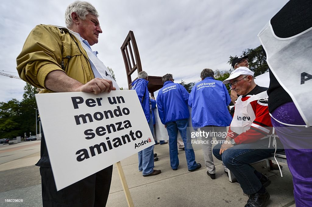 A victims of cancer-causing asbestos holds a placard reading in Italian 'For a World without asbestos' stages a protest on May 7, 2013 at the place des Nations facing the United Nations office in Geneva. Several national associations for the defence of the asbestos victims staged a protest during the 6th metting of the Rotterdam conventions for the listing of chrysotile asbestos on the list of dangerous products. AFP PHOTO / FABRICE COFFRINI