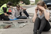 People sitting on the road after car crash
