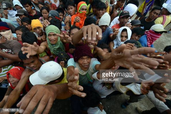 Victims of devastating Typhoon Bopha jostle for position as they beg for relief food being distributed by members of a private company in New Bataan...