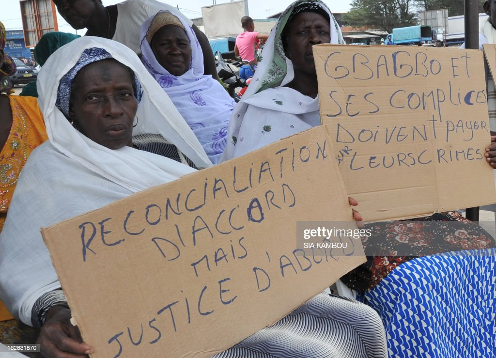 Victims of the 2010 post-election crisis hold placards reading 'Gbagbo and accomplices have to pay for their crimes, reconciliation ok but justice first' during a gathering in the Kouassai popular district of Abidjan on February 28, 2013. Former Ivory Coast president Laurent Gbagbo is expected to address the International Criminal Court on the final day of hearings today to decide whether he should face trial for crimes against humanity during the bloody 2010-2011 election standoff.