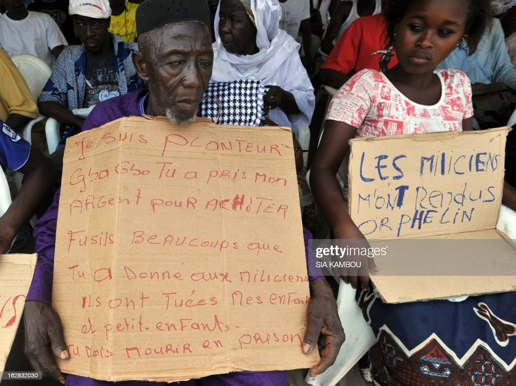 Victims of the 2010 post-election crisis hold placards reading 'I am a farmer, Gbagbo you took my money to buy rifles a lot that you gave to militiamen, they killed my children and grand children, you must die in jail' (at L) and 'Militiamen turned me into an orphan' (at R) during a gathering in the Kouassai popular district of Abidjan on February 28, 2013. Former Ivory Coast president Laurent Gbagbo is expected to address the International Criminal Court on the final day of hearings today to decide whether he should face trial for crimes against humanity during the bloody 2010-2011 election standoff.