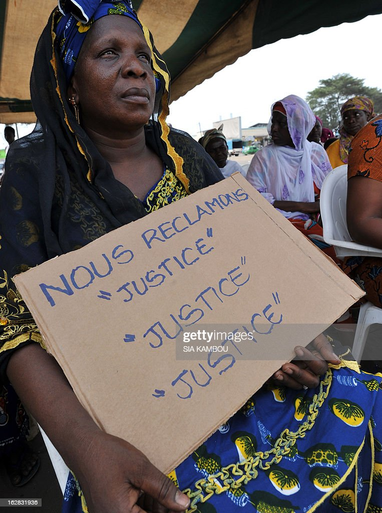 Victims of the 2010 post-election crisis hold placards reading 'We claim justice, justice justice' during a gathering in the Kouassai popular district of Abidjan on February 28, 2013. Former Ivory Coast president Laurent Gbagbo is expected to address the International Criminal Court on the final day of hearings today to decide whether he should face trial for crimes against humanity during the bloody 2010-2011 election standoff.