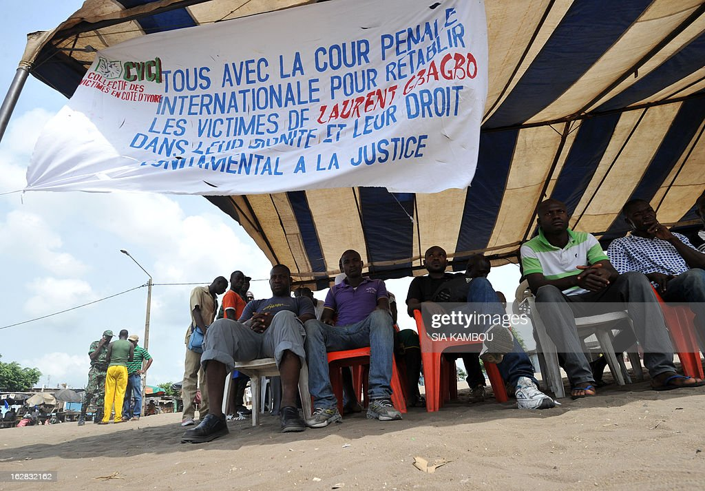 Victims of the 2010 post-election crisis hold sit under a banner reading 'All with the International Criminal Court to restore the victims of Laurent Gbagbo into their unity and their fundamental right to justice' during a gathering in the Kouassai popular district of Abidjan on February 28, 2013. Former Ivory Coast president Laurent Gbagbo is expected to address the International Criminal Court on the final day of hearings today to decide whether he should face trial for crimes against humanity during the bloody 2010-2011 election standoff. AFP PHOTO/ SIA KAMBOU