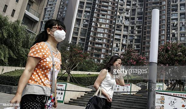 Victims of the explosions carrying their belongings walk out of their home in a residential area near the site of the explosions in Tianjin on August...