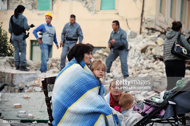 TOPSHOT Victims sit among the rubble of a house after a strong earthquake hit Amatrice on August 24 2016 Central Italy was struck by a powerful...