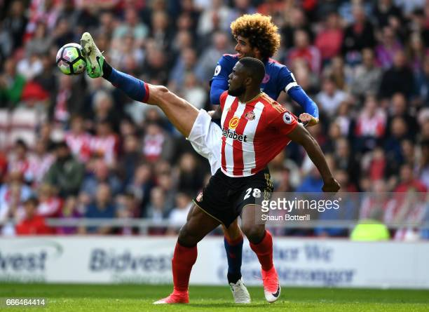 Victor Anichebe of Sunderland is tackled by Marouane Fellaini of Manchester United during the Premier League match between Sunderland and Manchester...