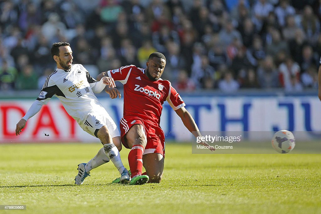 Victor Anichebe of West Bromwich Albion fouls Leon Britton of Swansea and earns a yellow card during the Barclays Premier League match between Swansea City and West Bromwich Albion at The Liberty Stadium on March 15, 2014 in Swansea, Wales.