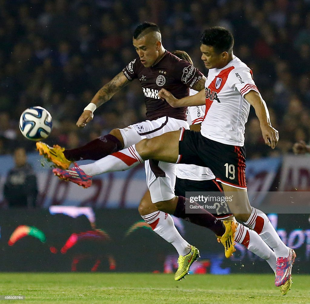 Victor Ayala of Lanus fights (L) for the ball with <a gi-track='captionPersonalityLinkClicked' href=/galleries/search?phrase=Teofilo+Gutierrez&family=editorial&specificpeople=5901237 ng-click='$event.stopPropagation()'>Teofilo Gutierrez</a> (R) of River Plate during a match between Lanus and River Plate as part of ninth round of Torneo de Transicion 2014 at Ciudad de Lanus Stadium on September 28, 2014 in Buenos Aires, Argentina.
