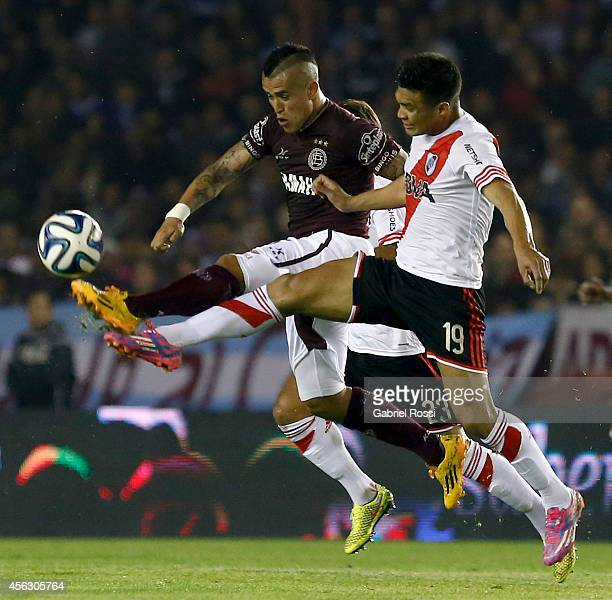 Victor Ayala of Lanus fights for the ball with Teofilo Gutierrez of River Plate during a match between Lanus and River Plate as part of ninth round...