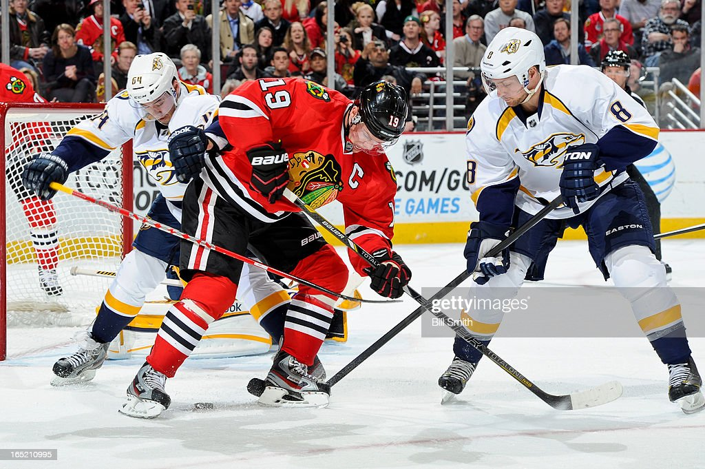 Victor Bartley #64 of the Nashville Predators and <a gi-track='captionPersonalityLinkClicked' href=/galleries/search?phrase=Jonathan+Toews&family=editorial&specificpeople=537799 ng-click='$event.stopPropagation()'>Jonathan Toews</a> #19 of the Chicago Blackhawks battle for the puck as Kevin Klein #8 of the Predators reaches in from the right during the NHL game on April 01, 2013 at the United Center in Chicago, Illinois.