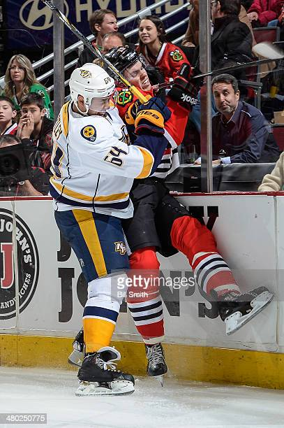 Victor Bartley of the Nashville Predators checks Jeremy Morin of the Chicago Blackhawks into the boards during the NHL game on March 23 2014 at the...