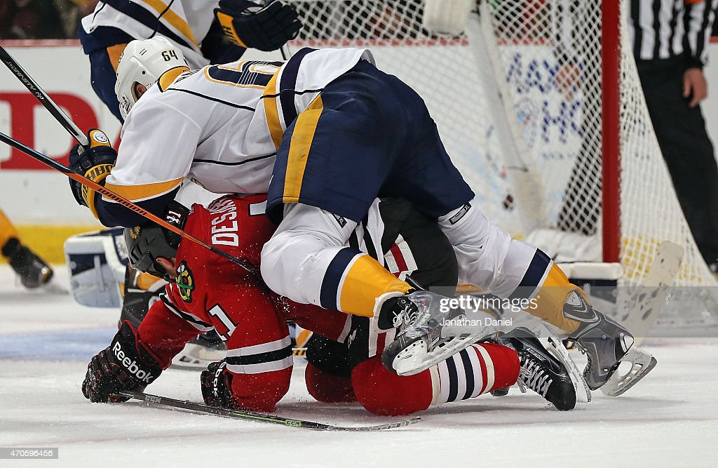 Victor Bartley #64 of the Nashville Predators lands on top of Andrew Desjardins #11 of the Chicago Blackhawks in Game Four of the Western Conference Quarterfinals during the 2015 NHL Stanley Cup Playoffs at the United Center on April 21, 2015 in Chicago, Illinois.