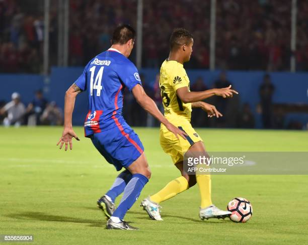 Victor Caceres of Paraguays Cerro Porteno vies for the ball with Wilmar Barrios of Argentina's Boca Juniors during a friendly match for the...