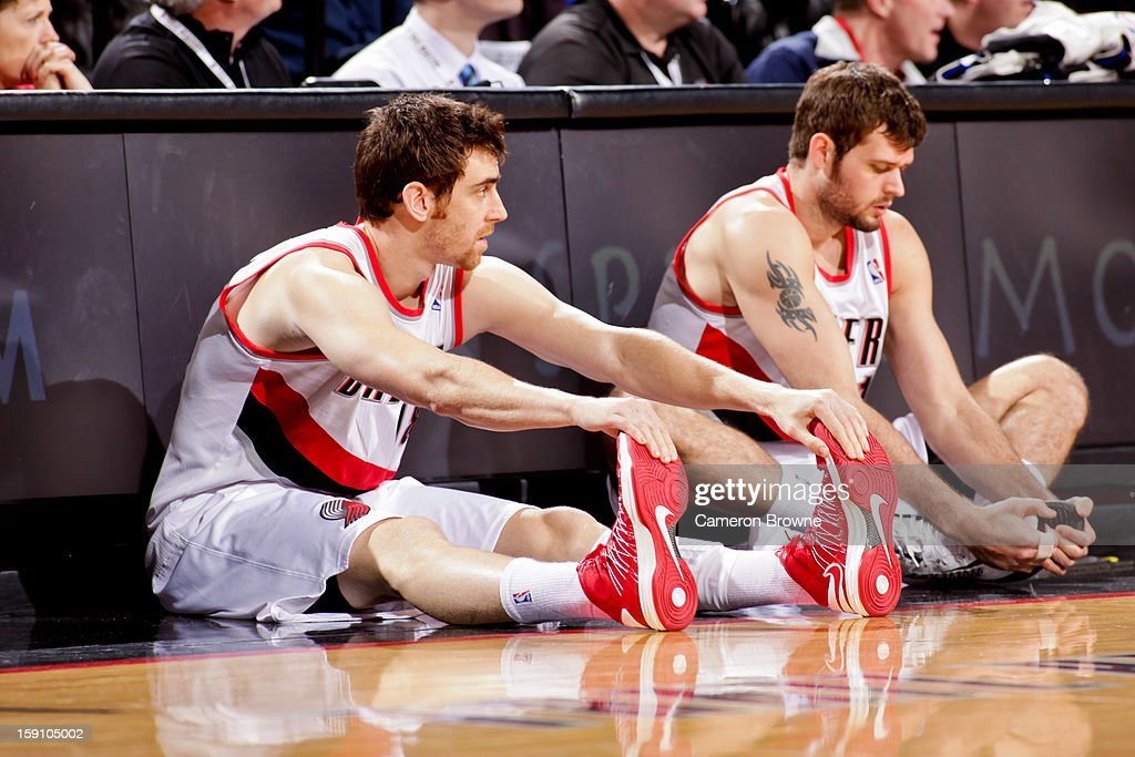 Victor Claver #18 and Joel Freeland #19 of the Portland Trail Blazers stretch on the sideline before checking into a game against the Orlando Magic on January 7, 2013 at the Rose Garden Arena in Portland, Oregon.