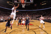 Victor Claver of the Portland Trail Blazers shoots a layup against Alec Burks of the Utah Jazz on March 29 2013 at the Rose Garden Arena in Portland...