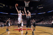 Victor Claver of the Portland Trail Blazers shoots against Mason Plumlee of the Brooklyn Nets on February 26 2014 at the Moda Center Arena in...