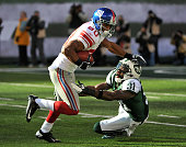 Victor Cruz of the New York Giants breaks the tackle attempt of Antonio Cromartie of the New York Jets during the first half on December 24 2011 at...