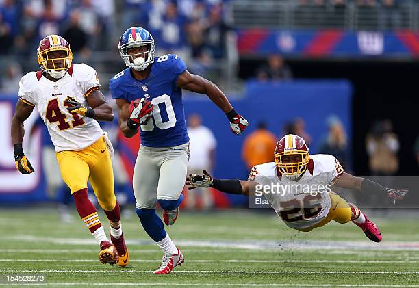 Victor Cruz of the New York Giants carries the ball past Madieu Williams and Josh Wilson of the Washington Redskins to score the game winning...