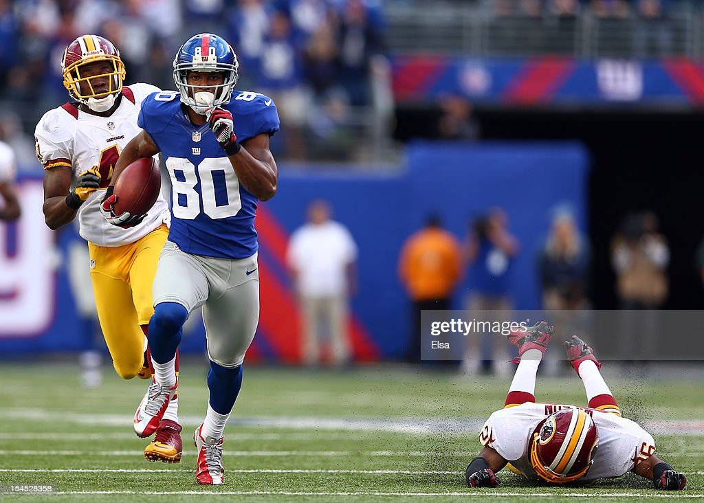 Victor Cruz #80 of the New York Giants carries the ball past Madieu Williams #41 and Josh Wilson #26 of the Washington Redskins to score the game winning touchdown on October 21, 2012 at MetLife Stadium in East Rutherford, New Jersey.The New York Giants defeated the Washington Redskins 27-23.