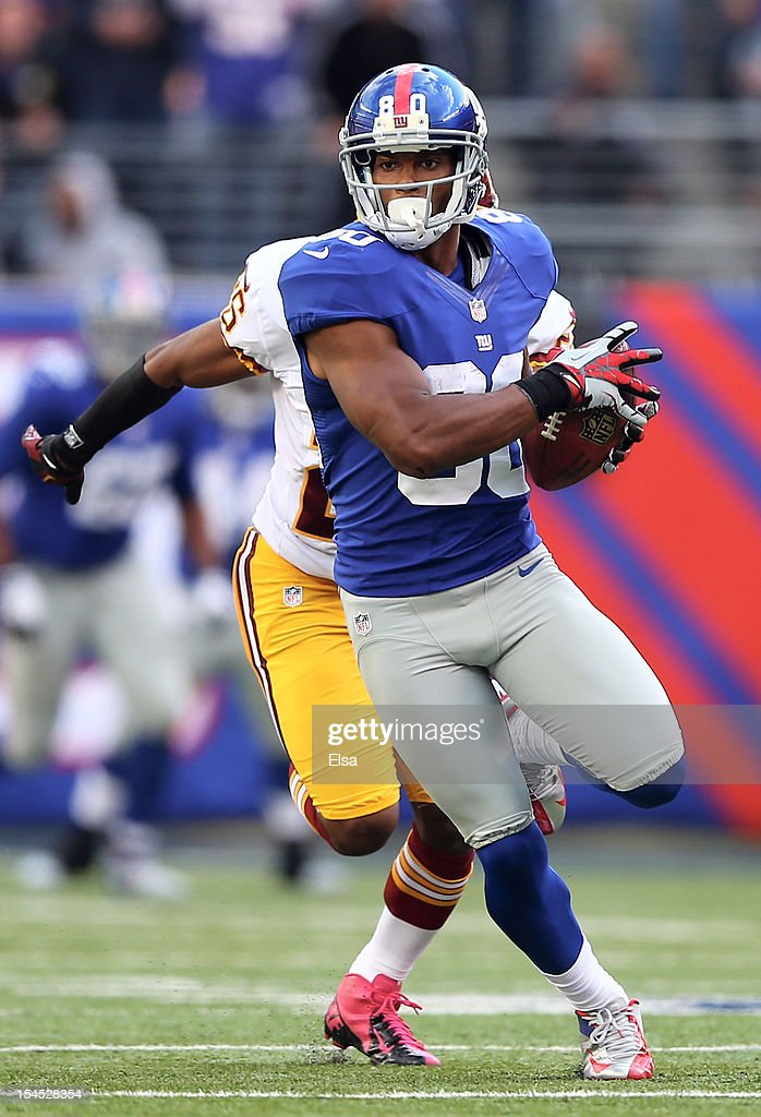 Victor Cruz #80 of the New York Giants carries the ball past Madieu Williams #41 of the Washington Redskins to score the game winning touchdown on October 21, 2012 at MetLife Stadium in East Rutherford, New Jersey.The New York Giants defeated the Washington Redskins 27-23.