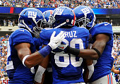 Victor Cruz of the New York Giants celebrates his touchdown against the Houston Texans with teammates in the second quarter at MetLife Stadium on...