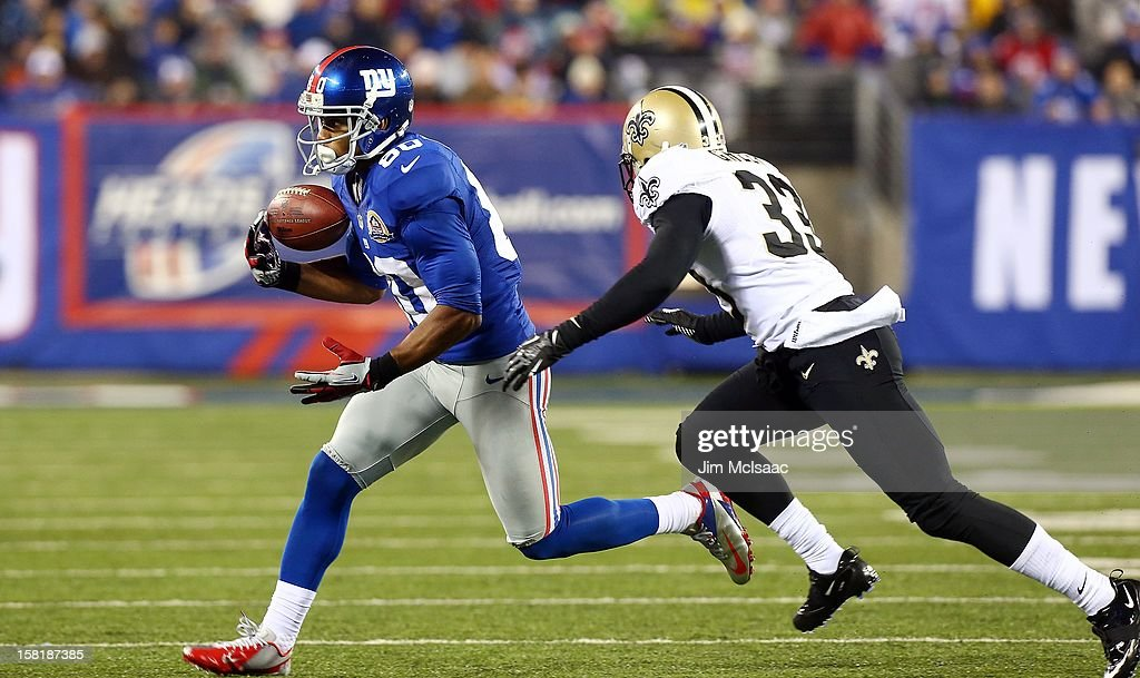 Victor Cruz #80 of the New York Giants in action against Jabari Greer #33 of the New Orleans Saints at MetLife Stadium on December 9, 2012 in East Rutherford, New Jersey. The Giants defeated the Saints 52-27.