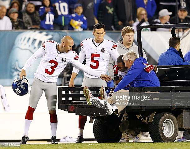 Victor Cruz of the New York Giants is carted off the field as teammates Josh Brown and Steve Weatherford console him after attempting a catch in the...