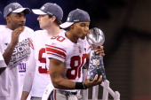 Victor Cruz of the New York Giants kisses the Vince Lombardi Trophy after defeating the New England Patriots in Super Bowl XLVI at Lucas Oil Stadium...