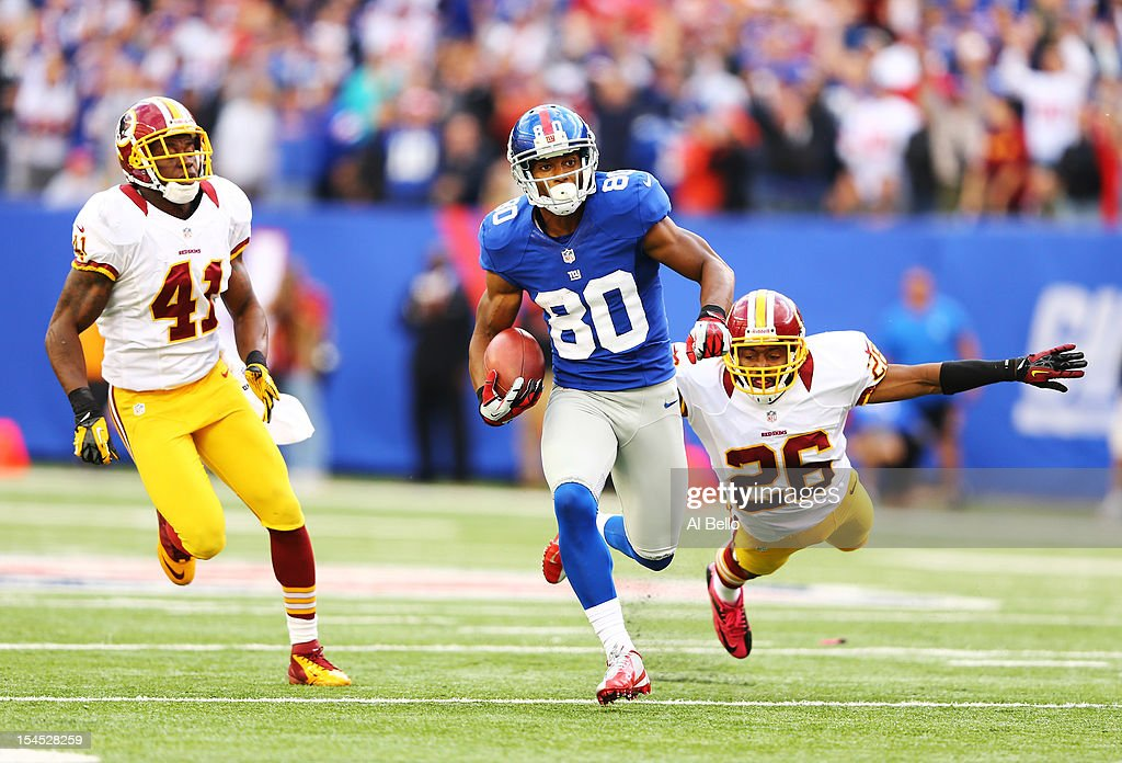 Victor Cruz #80 of the New York Giants runs after a catch for the winning touchdown as Madieu Williams #41, and Josh Wilson #26 of the Washington Redskins give chase in the fourth quarter of a 27-23 Giant win at MetLife Stadium on October 21, 2012 in East Rutherford, New Jersey.