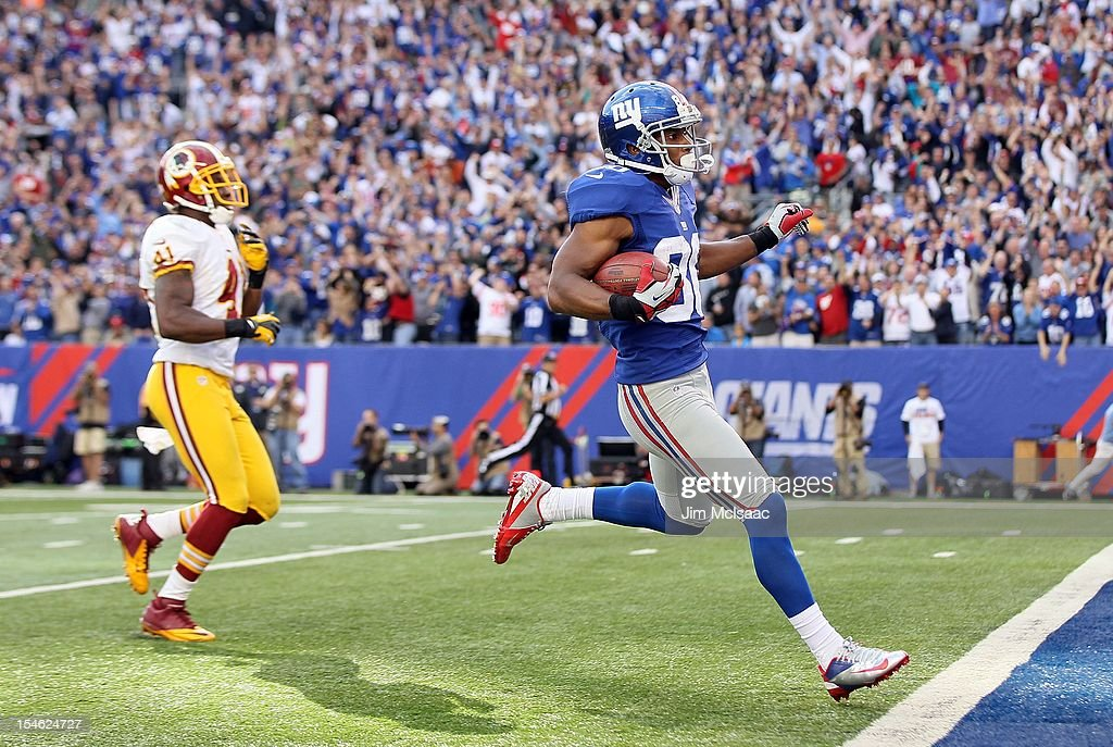 Victor Cruz #80 of the New York Giants runs in a touchdown reception late in the fourth quarter against Madieu Williams #41 of the Washington Redskins at MetLife Stadium on October 21, 2012 in East Rutherford, New Jersey. The Giants defeated the Redskins 27-23.