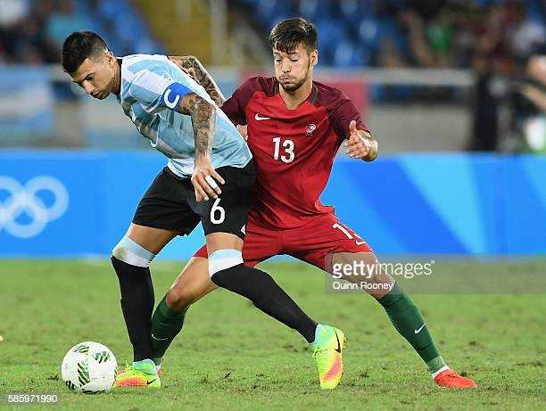 Victor Cuesta of Argentina and Trabulo Pite of Portugal compete for the ball during the Men's Group D first round match between Portugal and...