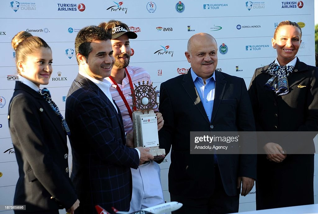 Victor Dubuisson (C) of France is awarded the trophy by Hamdi Topcu (2nd R), Chairman of the Board of Turkish Airlines and Turkish Youth and Sports Minister Suat Kilic (2nd L) after winning the 'Turkish Airlines Open Golf Tournament' of PGA European Tour Final Series on November 10, 2013 in Antalya, Turkey.