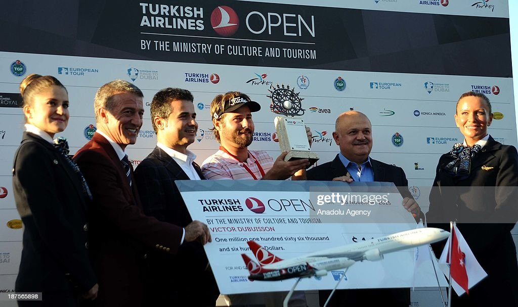 Victor Dubuisson (C) of France is awarded the trophy by Turkish Youth and Sports Minister Suat Kilic (3rd L) and Hamdi Topcu (2nd R), Chairman of the Board of Turkish Airlines after winning the 'Turkish Airlines Open Golf Tournament' of PGA European Tour Final Series on November 10, 2013 in Antalya, Turkey.