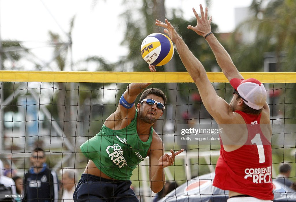 Victor Felipe (in green) of Brazil smashes the ball as Jonas Kissling (in red) of Switzerland tries to block during a match between Brazil and Switzerland as part of day one of Corrientes Grand Slam of FIVB World Tour at Arazaty Beach on May 22, 2013 in Corrientes, Argentina.